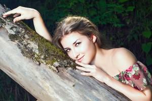 אישה נשענת על עץ